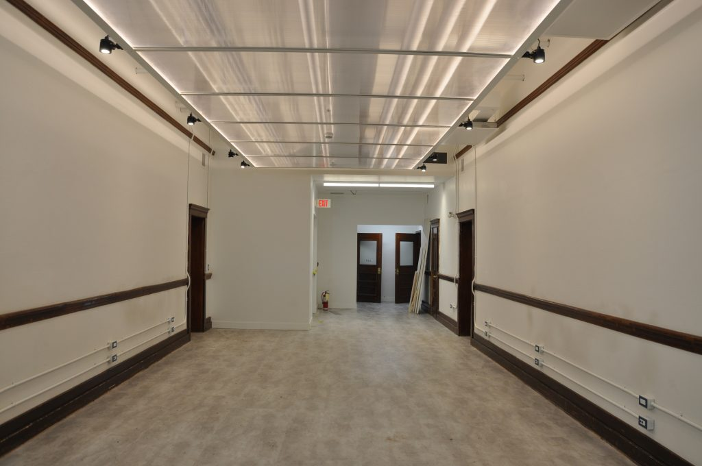 "The hallways have been outfitted with ceiling ""cloud"" transparent polycarbonate panels and flexible gallery lighting to ensure the hallway gallery spaces become the perfect backdrops for shows, exhibitions and sales."